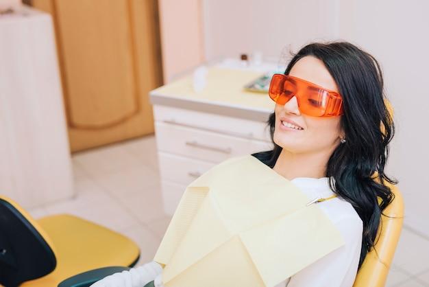 Paciente do sexo feminino sentado no consultório odontológico