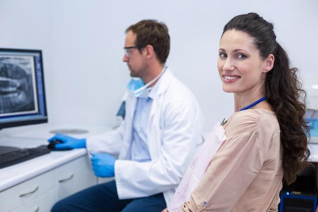 Paciente do sexo feminino sorrindo para a câmera enquanto dentista olhando para um raio-x