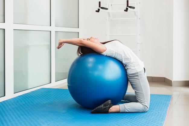 Paciente do sexo feminino usando bola de exercício