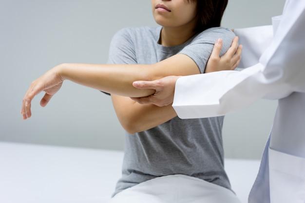 Paciente do sexo feminino vem ver um médico para verificar se há dor no cotovelo