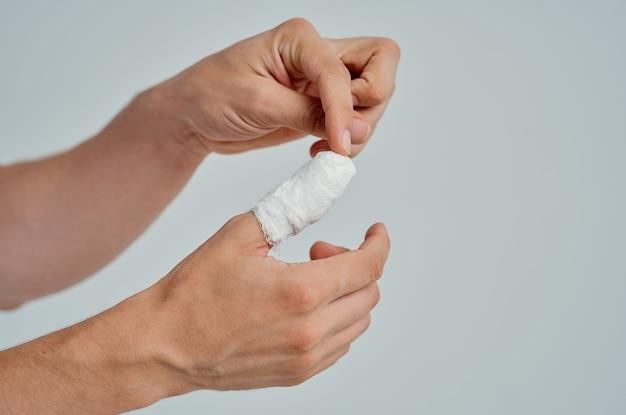 Paciente do sexo masculino com curativo ferimento na mão nos dedos luz de fundo