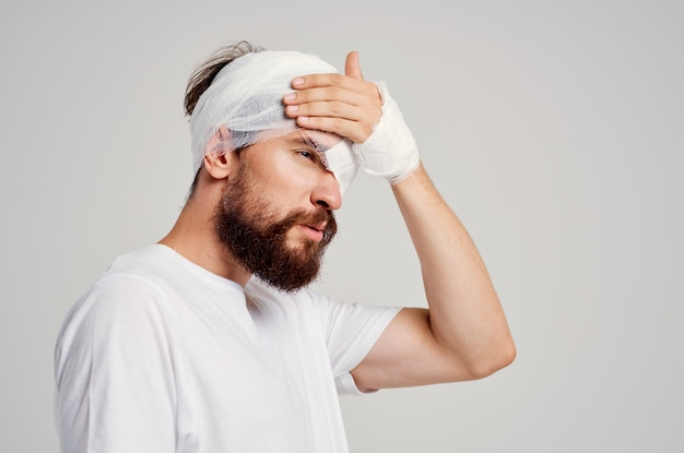 Paciente do sexo masculino com traumatismo cranioencefálico em camiseta branca com luz de fundo de dor de cabeça
