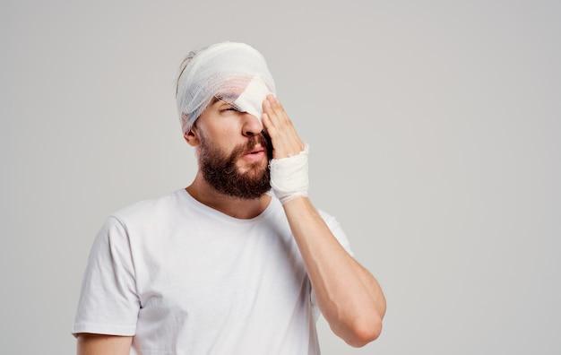 Paciente do sexo masculino com traumatismo cranioencefálico em uma camiseta branca com luz de fundo de dor de cabeça