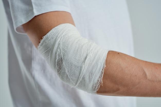 Paciente do sexo masculino com uma camiseta branca e um fundo isolado à mão enfaixado