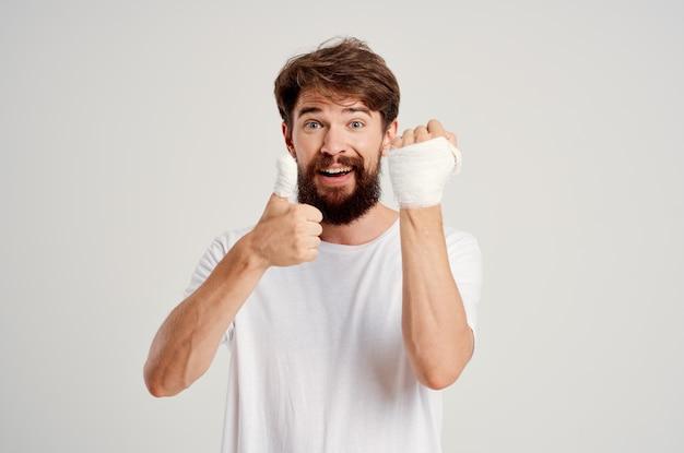 Paciente do sexo masculino com uma camiseta branca e uma mão enfaixada posando com remédio hospitalar