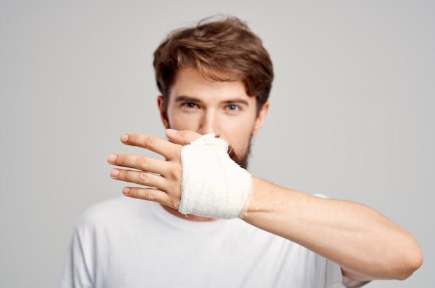 Paciente do sexo masculino com uma camiseta branca e uma mão enfaixada posando com um fundo isolado