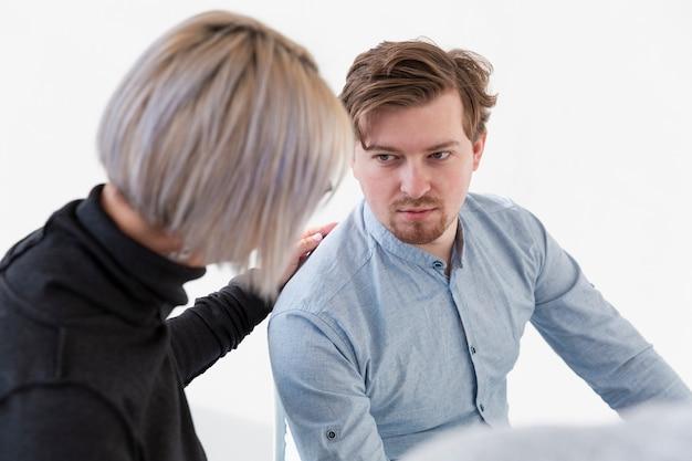 Paciente do sexo masculino olhando para médico de reabilitação