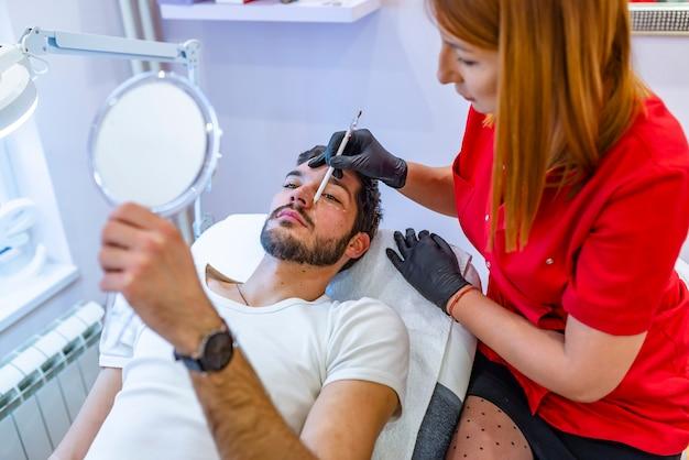 Paciente do sexo masculino pacífica com linhas de correção no rosto em uma sala de exame.