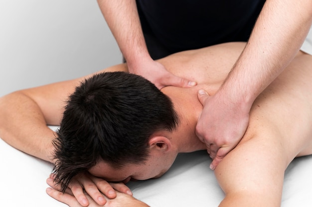 Paciente do sexo masculino recebendo massagem nas costas do fisioterapeuta