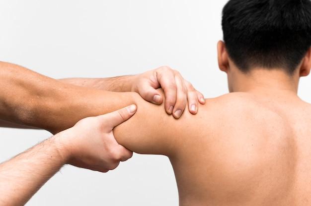 Paciente do sexo masculino recebendo massagem no ombro do fisioterapeuta