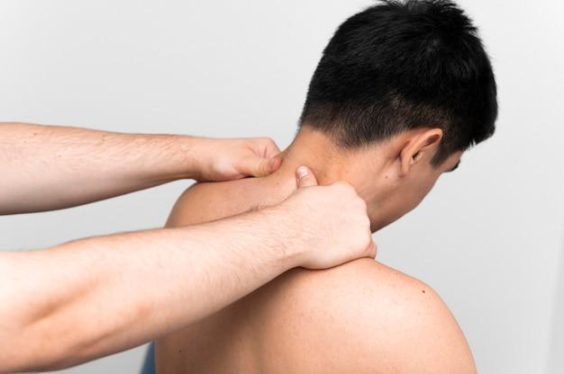 Paciente do sexo masculino recebendo massagem no pescoço do fisioterapeuta