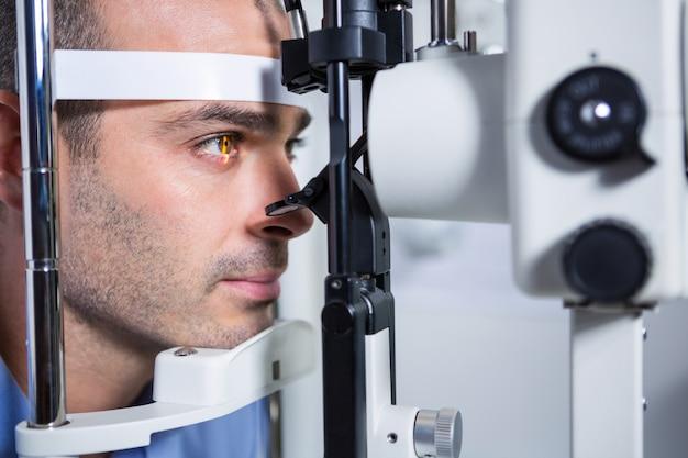 Paciente do sexo masculino recebendo sua córnea verificada com lâmpada de fenda