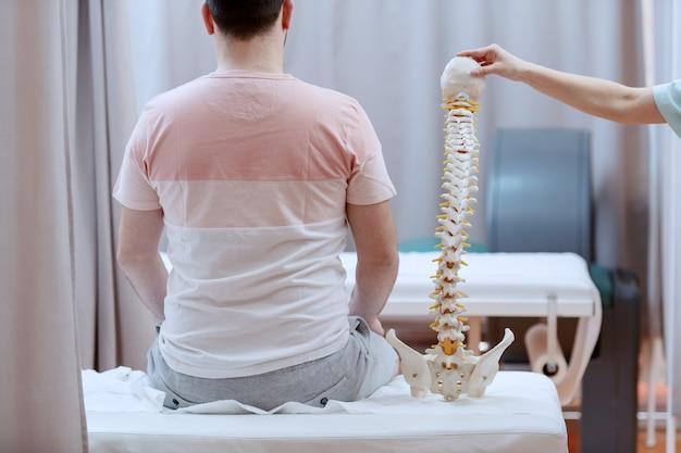 Paciente do sexo masculino sentado na cama do hospital com as costas viradas. ao lado dele está a enfermeira segurando o modelo da coluna.