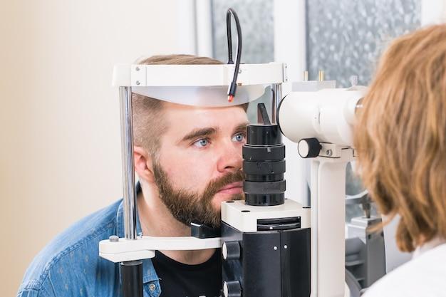 Paciente do sexo masculino tendo a visão do olho examinada por um oftalmologista