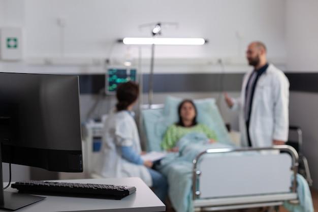 Paciente doente descansando na cama usando tubo de oxigênio nasal enquanto discute com médicos tratadores ...