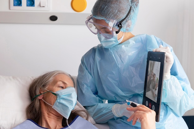 Paciente doente do sexo feminino na cama no hospital conversando com a família por meio de um tablet