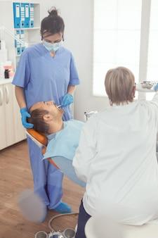 Paciente doente em pé na cadeira de estomatologia com a boca aberta