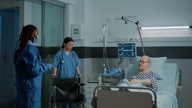 Paciente doente sentado em cadeira de rodas na enfermaria do hospital na clínica
