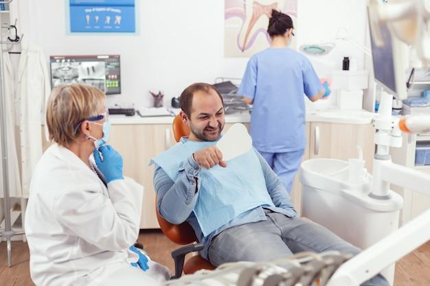 Paciente doente verificando dentes saudáveis e analisando procedimento cirúrgico