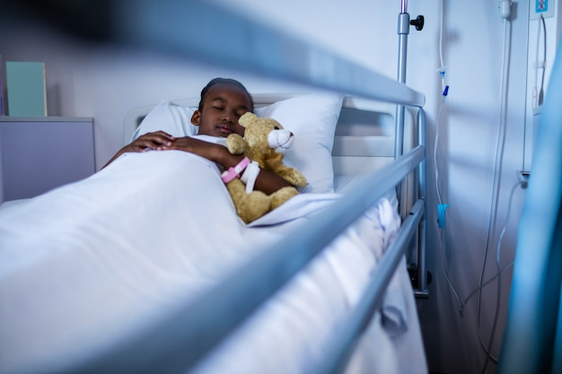 Paciente dormindo com ursinho de pelúcia na cama