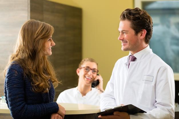 Paciente e área de recepção de documentos do consultório médico ou dentista, ele segura uma prancheta, a recepcionista está no telefone