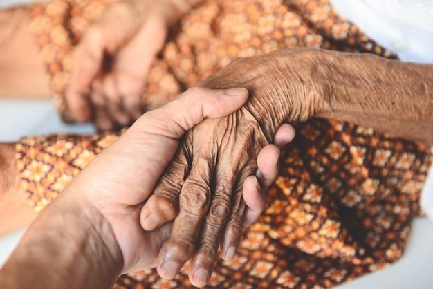 Paciente e enfermeira sênior medição de pulso à mão