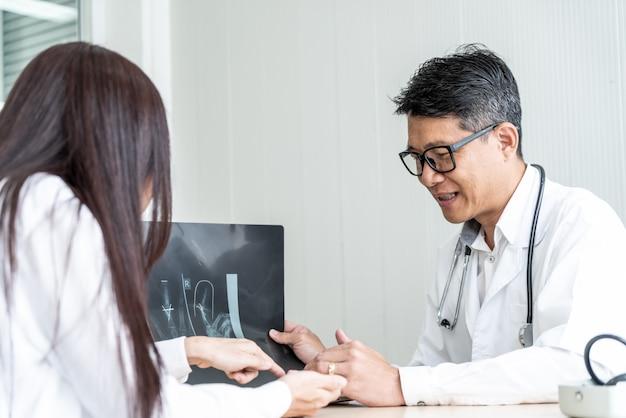 Paciente e médico asiático estão discutindo