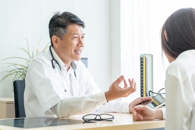 Paciente e médico sênior asiáticos estão discutindo