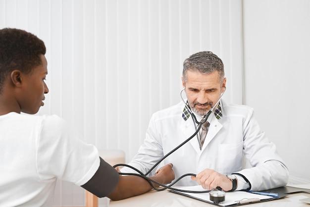 Paciente em gabinete médico na medição da pressão arterial.
