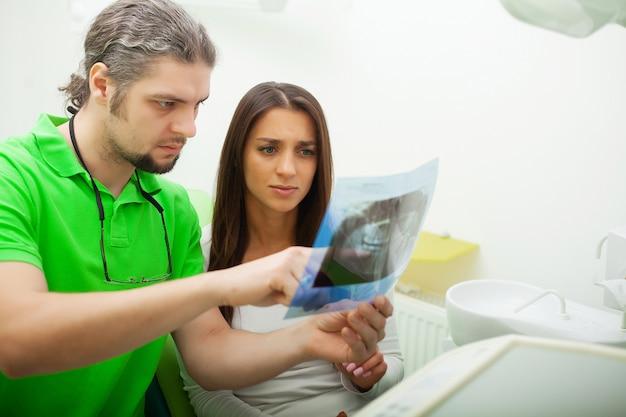Paciente em odontologia. mulher bonita, visitando seu dentista na clínica
