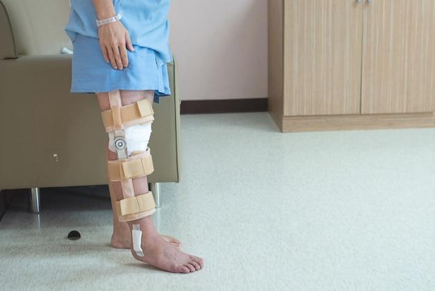 Paciente em pé com apoio da cinta de joelho e gesso após cirurgia do joelho do ligamento pcl no hospital da enfermaria ortopédica, recuperação e conceito de saúde.