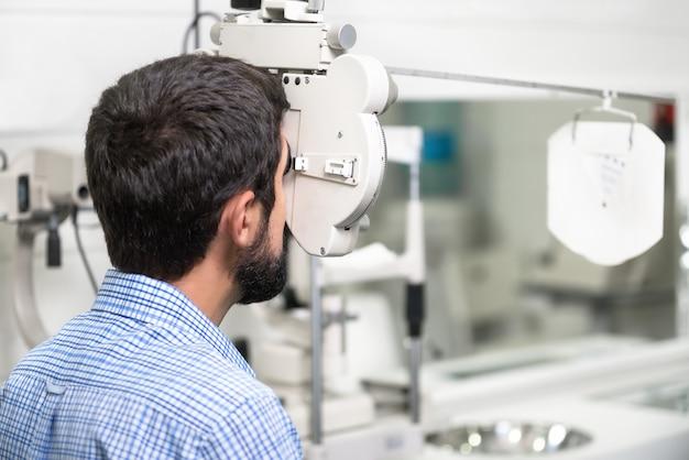 Paciente está lendo o gráfico optometrista na moderna clínica de oftalmologia.