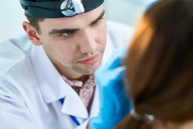Paciente examinando jovem otorrinolaringologista