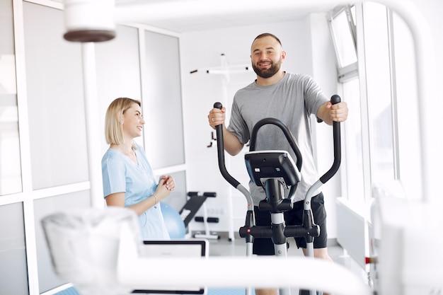 Paciente fazendo exercício em bicicleta de spin no ginásio com terapeuta