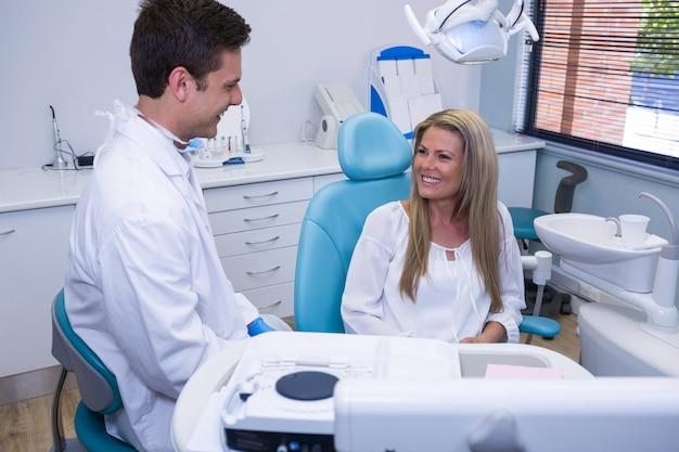 Paciente feliz conversando com dentista
