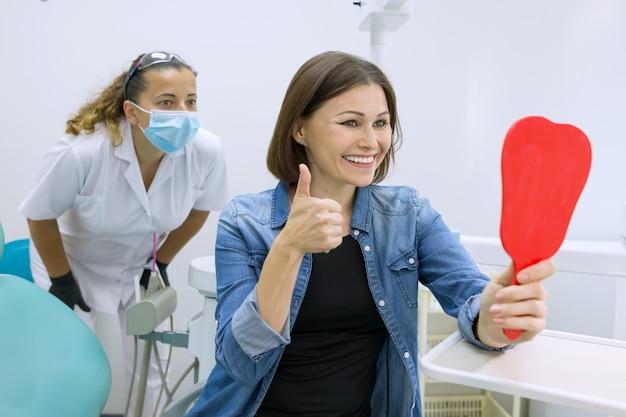 Paciente feliz da mulher que olha no espelho nos dentes, sentando-se na cadeira dental.