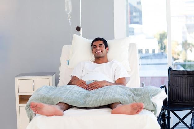 Paciente hispânico na cama sorrindo para a câmera