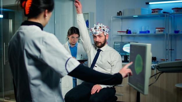 Paciente homem com fone de ouvido de alta tecnologia participando de experimento neurológico em testes laboratoriais tecnologicamente avançados, reações físicas e sistema nervoso