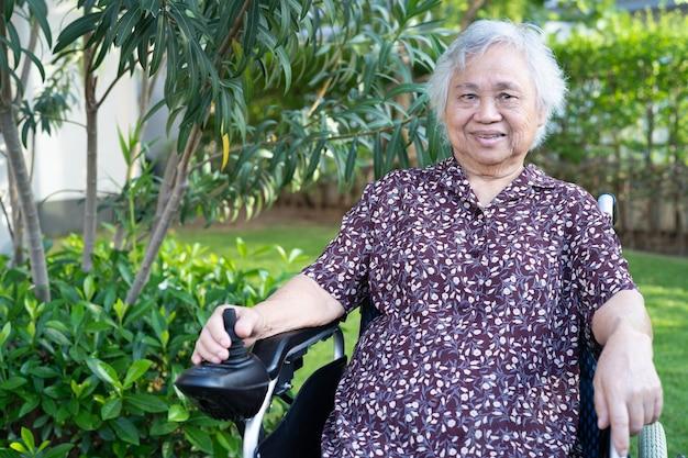 Paciente idosa asiática em cadeira de rodas elétrica com controle remoto