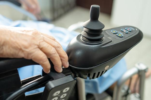 Paciente idosa asiática em cadeira de rodas elétrica w