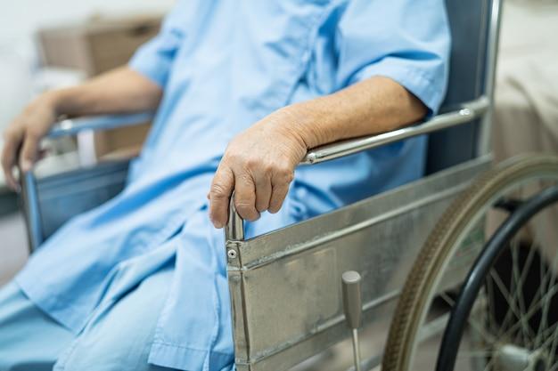 Paciente idosa asiática em cadeira de rodas em hospital de enfermagem
