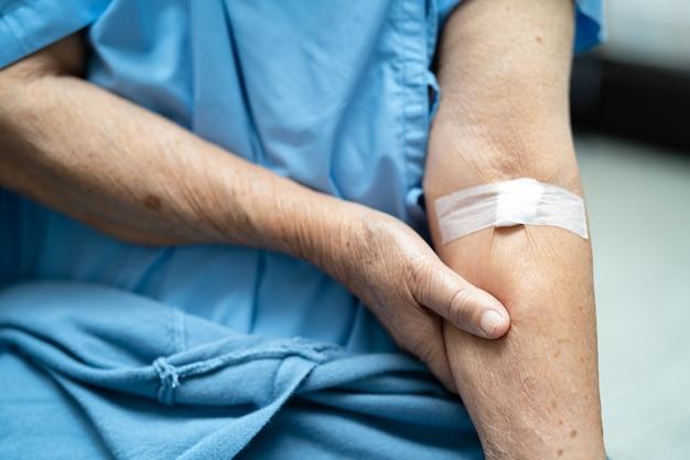 Paciente idosa asiática mostra algodão para parar de sangrar