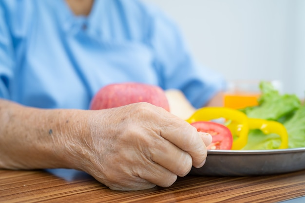Paciente idosa asiática tomando café da manhã com vegetais saudáveis
