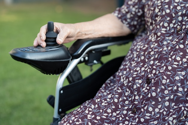 Paciente idosa ou idosa asiática em uma cadeira de rodas elétrica com controle remoto na enfermaria do hospital de enfermagem, conceito médico forte e saudável