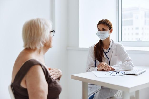 Paciente idosa se comunica com o estetoscópio do médico. foto de alta qualidade