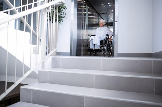 Paciente idoso com deficiência em cadeira de rodas no elevador