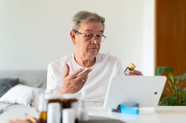 Paciente idoso de tiro médio com tablet