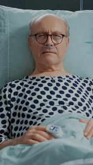 Paciente idoso doente na cama da enfermaria de hospital com tubo de oxigênio nasal
