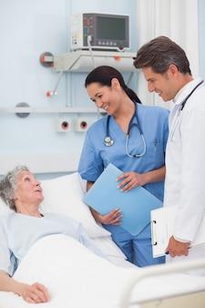 Paciente idoso falando com um médico e uma enfermeira