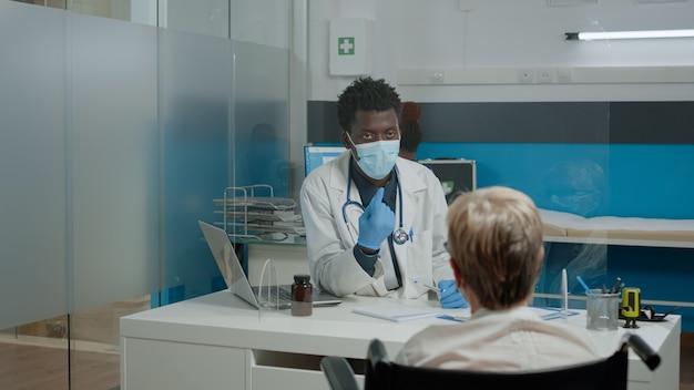 Paciente idoso inválido tendo consulta com o médico